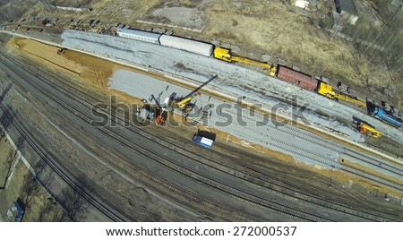Construction equipment and workers at the construction site of new railways, aerial view - stock photo
