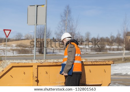 Construction foreman at the construction waste container - stock photo