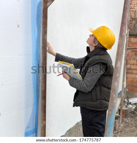 Construction inspector examine styrofoam insulation of house facade, wall - stock photo