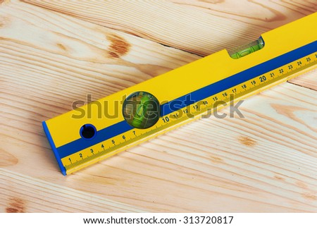 Construction Level on wooden background - stock photo