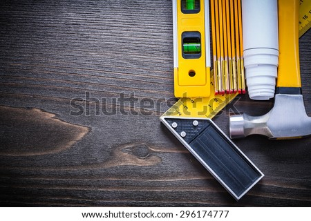 Construction level try square rolled blueprint wooden meter and claw hammer on vintage wood board architecture and building concept. - stock photo