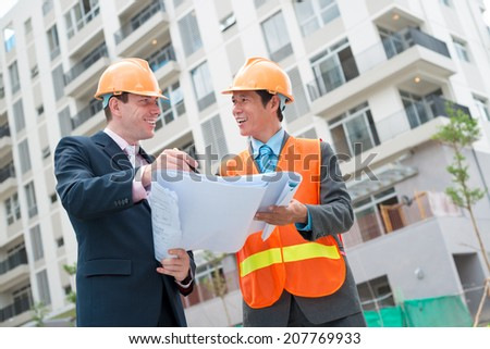 Construction manager and engineer discussing blueprint of the building - stock photo