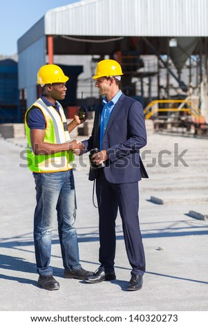construction manager and worker handshake on site - stock photo