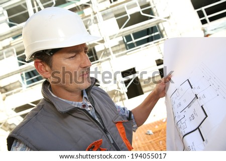 Construction manager on building site holding blueprint - stock photo