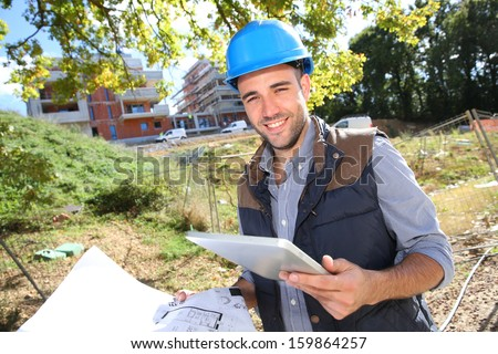Construction manager using tablet on building site - stock photo
