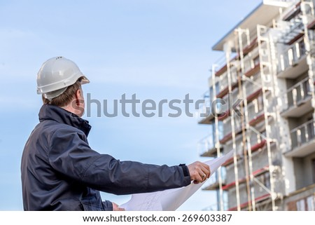 Construction manager with blueprints standing in front of construction site. - stock photo