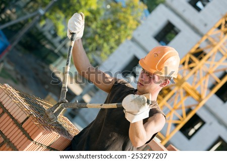 Construction manual bricklayer worker cutting armature grids with rebar cutters during masonry works - stock photo