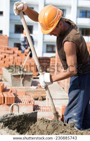 Construction manual bricklayer worker mixing concrete adhesive mixture with shovel during masonry works - stock photo
