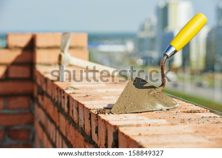 construction mason work tools. Brick trowel and pick hammer outdoors at building area - stock photo