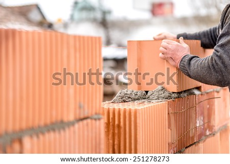 construction mason worker bricklayer installing brick walls - stock photo