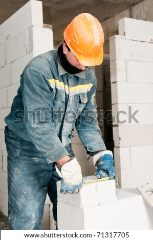 construction mason worker bricklayer measuring a brick with measure tape - stock photo