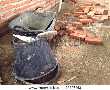 Construction masonry cement mortar tools on bucket - stock photo
