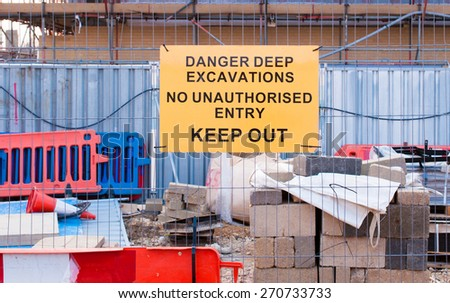 Construction material  in the background warning sign on metal fence - stock photo