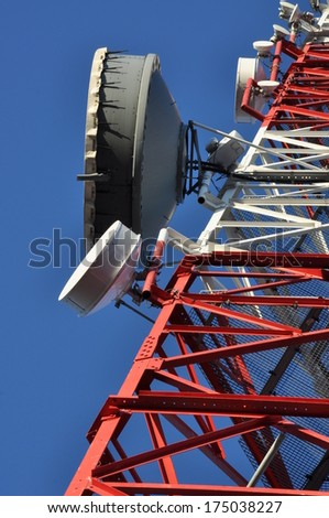 Construction of a telecommunications tower with antennas against a blue sky - stock photo