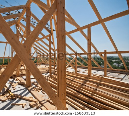 construction of a timber frame roof brick house, sunny day - stock photo