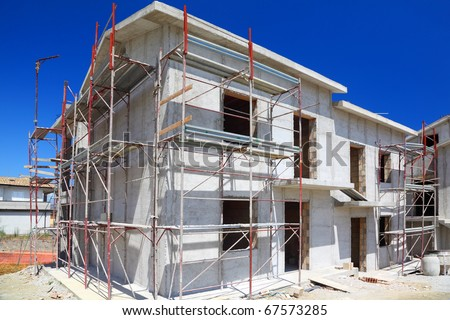 Construction of building of new two-story white concrete house with stairs and balcony - stock photo