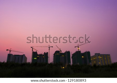 Construction of buildings in the capital,construction cranes and building silhouettes with Twilight - stock photo