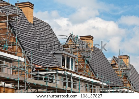 Construction of nearly finished family houses, build in a row - stock photo