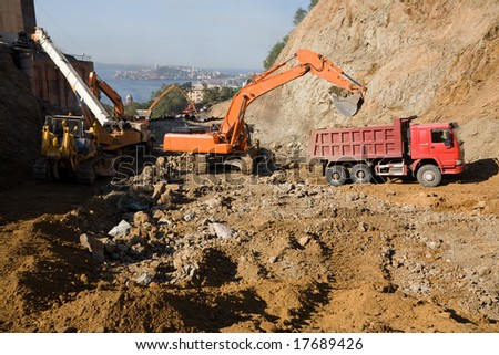 Construction of road in the middle cities.To quarry.On a background the sea & town. - stock photo