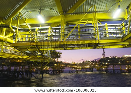 Construction of the lower decks of an offshore oil rig at night - stock photo