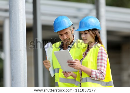 Construction people using electronic tablet on site - stock photo