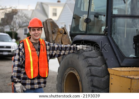 Construction road worker, standing next to tractor/bulldozer/excavator, his hand on the wheel. Residential area on the background. - stock photo