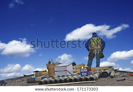 Construction Roofer Carpenter Worker on a Roof Preparing to Work. - stock photo