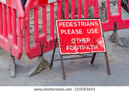 Construction sign standing on footpath, asking to use another footpath - stock photo