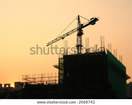 Construction Site at Dusk -- with crane and scaffolding - stock photo