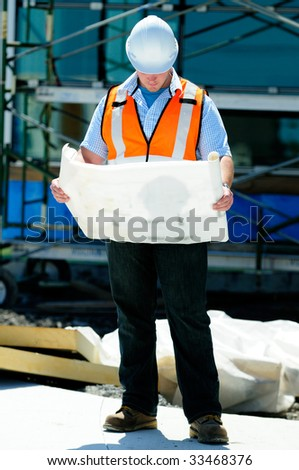 Construction Site Foreman, Checking The Blueprints Of A New Building - stock photo