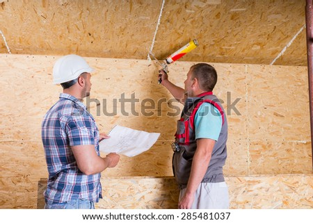 Construction Site Foreman Wearing White Hard Hat Holding Plans and Observing Worker Applying Caulking to Unfinished Wood Ceiling - stock photo