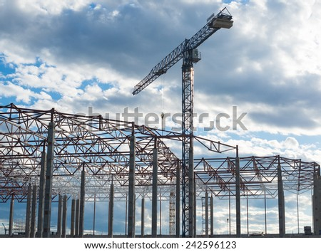 Construction site. Framework of the new building and tower crane above it. - stock photo