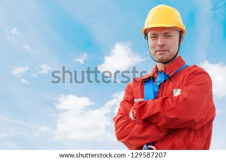 Construction site manager worker in uniform and safety protective equipment over blue sky - stock photo