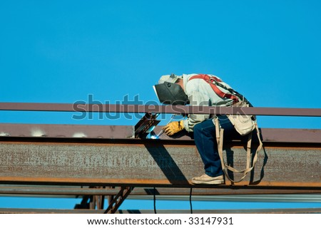 Construction site of a new building being erected. Welder sitting on top beam welding. - stock photo