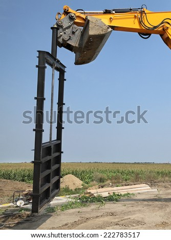Construction site of new irrigation channel in field, gate placing - stock photo