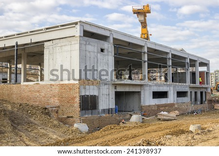 Construction site of supermarket with crane on sky background - stock photo