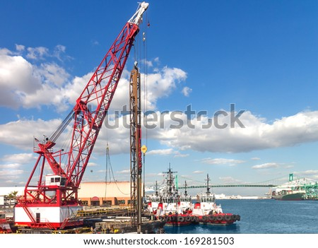 Construction site, port of Los Angeles. Heavy industrial hook and pulley crane working at harbor renovation. Boats, Vincent Thomas bridge in background. Blue sky with clouds. Horizontal scene. - stock photo