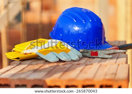 Construction site still life with hardhat, hammer and protective gloves - stock photo