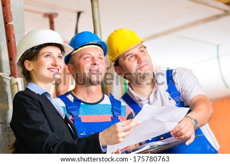 Construction site team or architect and builder or worker with helmets controlling or having discussion of plan or blueprint  - stock photo