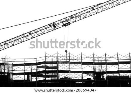 Construction site with crane and scaffolding seen as a silhouette - stock photo