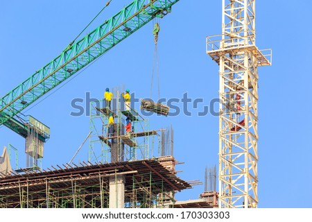Construction site with crane and workers on blue sky - stock photo