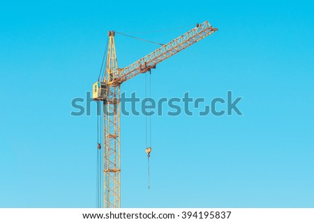 Construction site with cranes against blue sky - stock photo