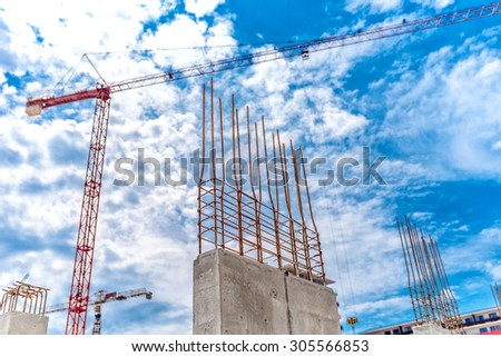 Construction site with industrial crane and close up of reinforced concrete walls, building of skyscraper office building - stock photo