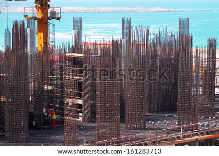 Construction site with worker in Dubai at the seaside - stock photo