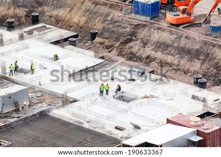 Construction site with workers making foundation - stock photo