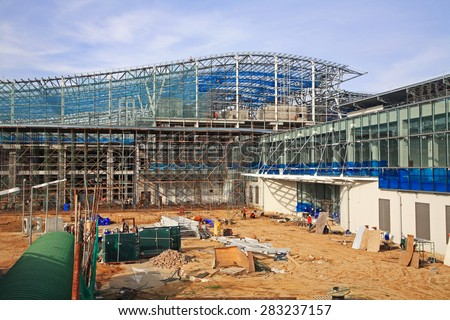 construction site with workers of unfinished airport terminal made by Sunlit glass - stock photo