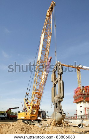 Construction site with yellow tractors.Big and yellow construction crane, heavy lifting - stock photo