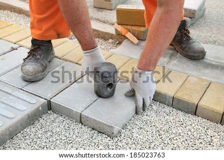 Construction site, worker installing concrete brick pavement, using hammer - stock photo