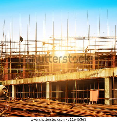 Construction site, workers and cranes. - stock photo