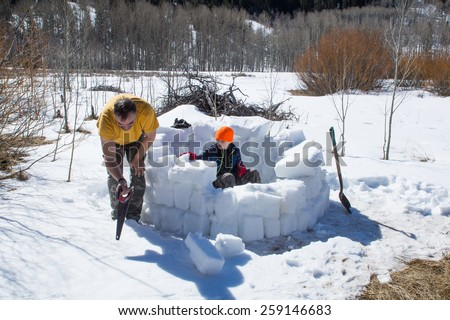Construction Stages igloo - Eskimo dwelling. Adult cuts bricks of ice crust, the child strengthens the inside wall of snow built - stock photo